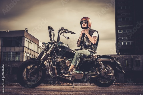 Fotografie, Tablou Tattooed biker and his bobber style motorcycle on a city streets