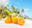 Orange juice on wooden with tropical beach