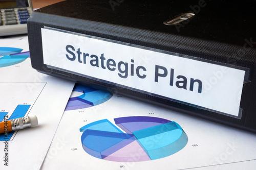 Fotografía  Graphs and file folder with label Strategic plan.