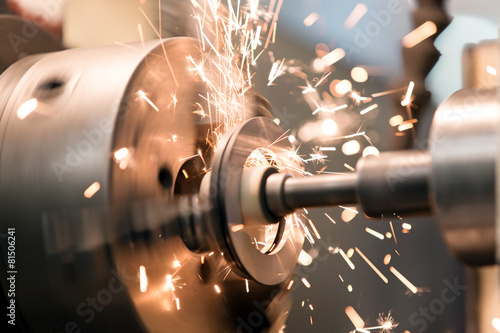 Fotografie, Obraz  Finishing metal working on lathe grinder machine with sparks