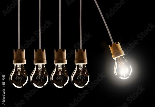 Light bulbs in row with single one shinning Fotobehang