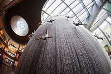 Waterfall In Dubai Mall With Sculptures Of Human Divers