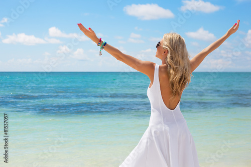 Fotografija  Young woman in white dress enjoying summer day on the beach