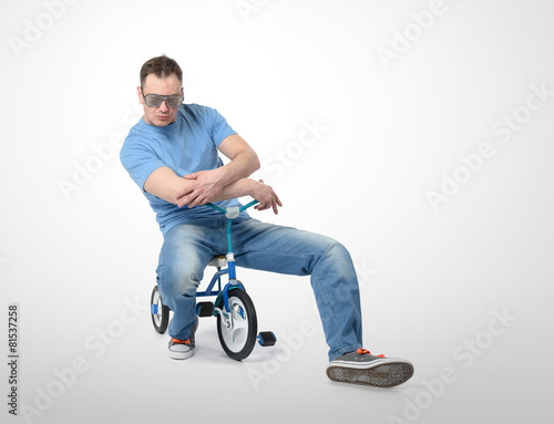 Cool man in a glamor glasses on children's bicycle Canvas Print