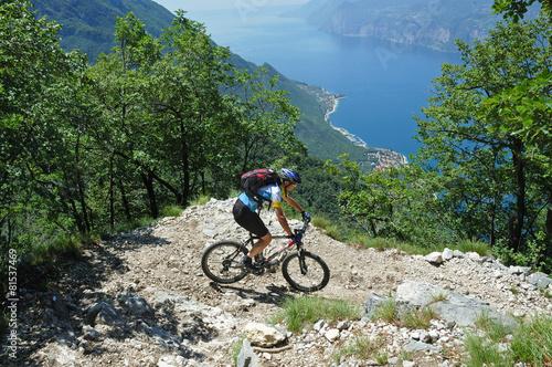 Foto op Plexiglas Fietsen Mountainbiker at the trail near Garda Lake