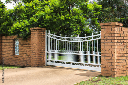 Fotografie, Obraz  White wrought iron driveway entrance gates in brick fence