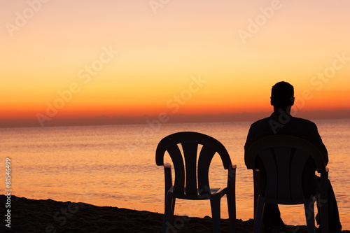 Fotografía  Man sits on chair alone in sunset