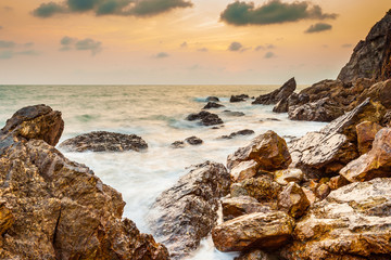 Fototapeta Morze Seascape coast of evening wave with rock and cloud on golden sky