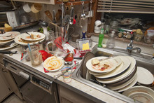 Dirty Dishes Over Flowing In A Kitchen Sink