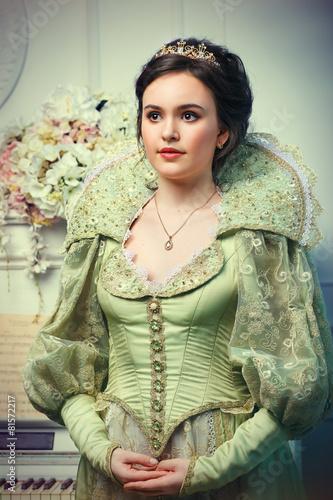 Foto  Königin im königlichen Kleid neben dem Klavier