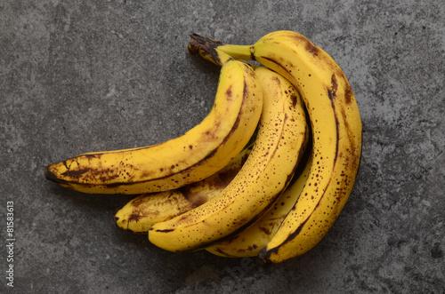 Valokuva  Bananas on dark, stone table