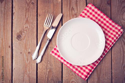 Foto  Leere Platte auf Tischdecke auf Holztisch. Blick von oben