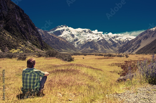 Fotografia  Man sitting on grass and looking at mountains