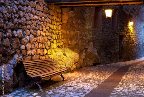 Banco en calle de pueblo iluminado por farolillos