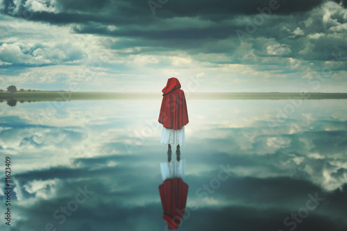 Foto Red hooded woman in a strange landscape with clouds
