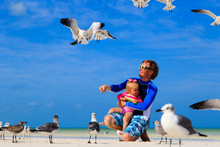 Father And Little Daugther Feeding Seagulls On The Beach