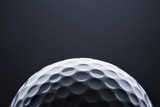 Macro golf ball on dark blue  background, space for text.