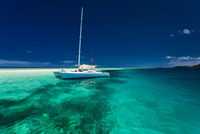 White Catamaran In Shallow Tropical Water With Snorkeling Reef