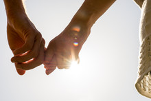 Couple Hands Holding Together With Sun Rays