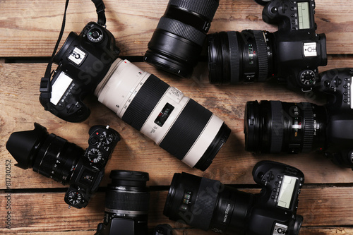 Modern cameras on wooden table, top view Wallpaper Mural