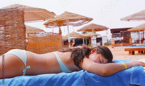 beautiful preteen girl in swimming suit lay on the beach take su