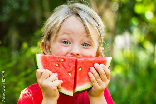 Fotografija Funny happy child eating watermelon outdoors