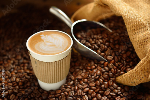 Wall Murals Cafe Paper cup of coffee latte and coffee beans on wooden table