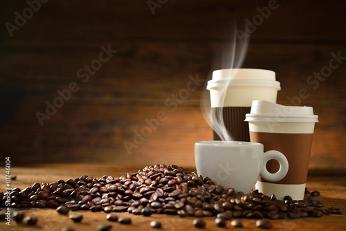 Spoed Foto op Canvas Cafe Cups of coffee and coffee beans on old wooden background