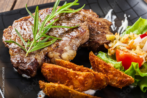 Papiers peints Steakhouse Portion of beef steak served with roast potatoes