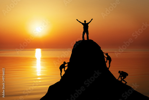 Fotomural Silhouette of a mans on a mountain top on sunset background.