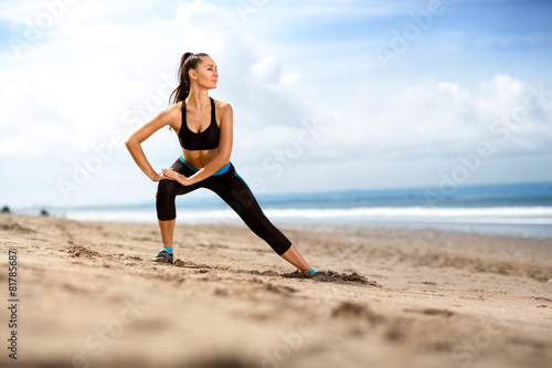 Láminas  Fit woman  doing exercises for legs on the beach