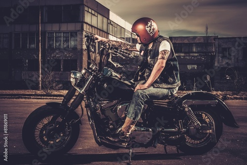 Fototapeta  Biker and his bobber style motorcycle on a city streets