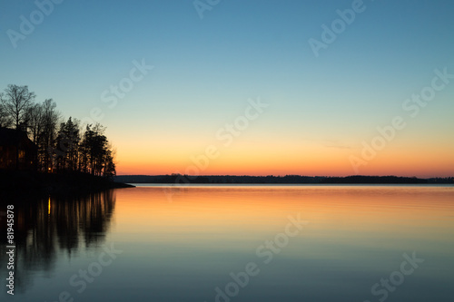 Fotografiet  Cabin on the point reflecting in the lake with spring sunset col