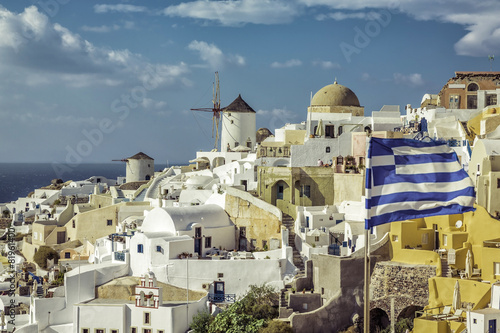 Fototapety, obrazy: Village of Oia against greek waving flag, Santorini ,Greece