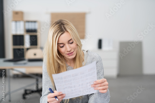 Fototapeta frau im büro liest konzentriert ein formular obraz