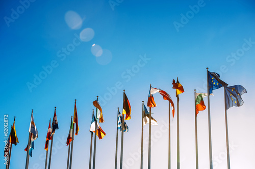 Foto  All European Union flags against blue sky in front of parliament