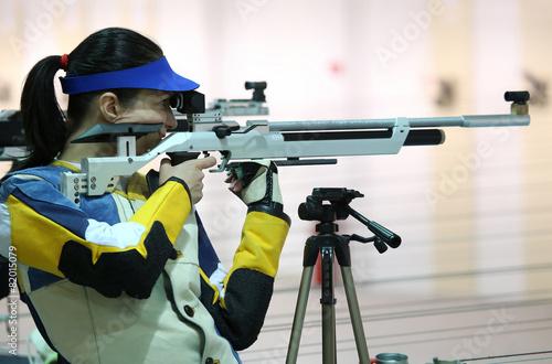Fotografía  woman aiming a pneumatic air rifle