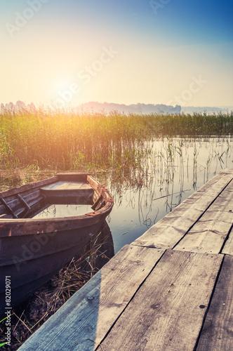Obraz Old boat on the coast of lake at sunset - fototapety do salonu