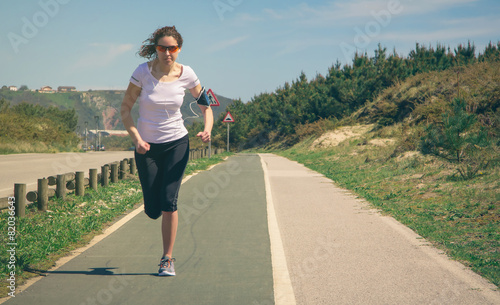 Papiers peints Young woman with earphones listening music and running