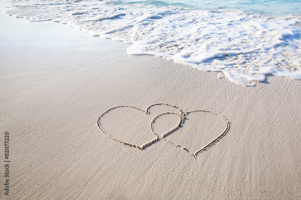 two hearts drawn on perfectly white sand of paradise beach