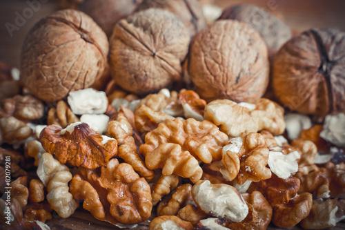 Keuken foto achterwand Baobab Walnut kernels and whole walnuts wood background