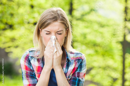 Photo  Woman with allergy symptom blowing nose