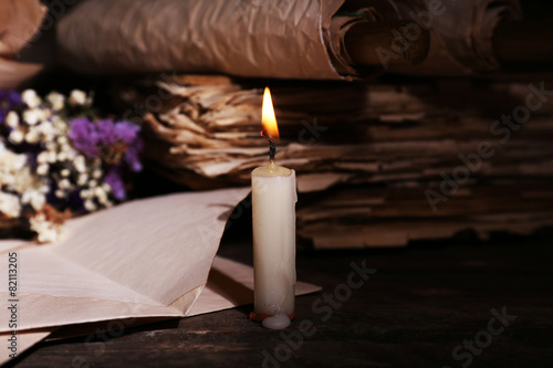 Fotografie, Tablou  Still life with retro books and candlelight on wooden table, closeup