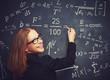 happy girl student, the teacher writes on blackboard chalk form
