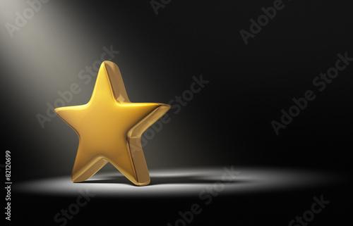 Fotografía Spotlight On Gold Star On Dark Background