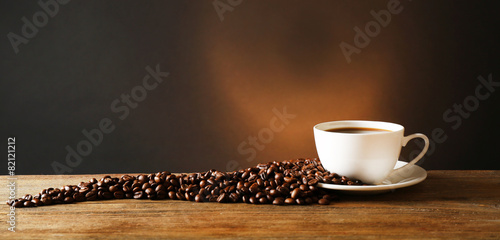 Deurstickers Cafe Cup of coffee with grains on wooden table on dark background