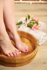 Obraz na płótnie Canvas Woman washing beautiful legs in bowl. Spa procedure concept