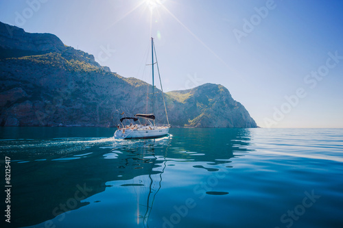 Yacht sailing along the shore the sea in calm weather.