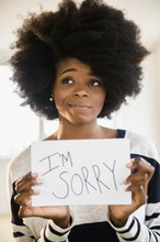 "Mixed Race Woman Holding ""I'm Sorry"" Sign"