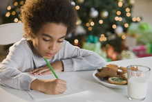Mixed Race Boy Writing Letter To Santa Claus